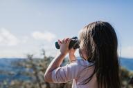 Girl looking through binoculars against sky - CAVF37631