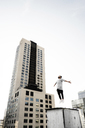 Low angle view of man jumping on building terrace against clear sky - CAVF37724