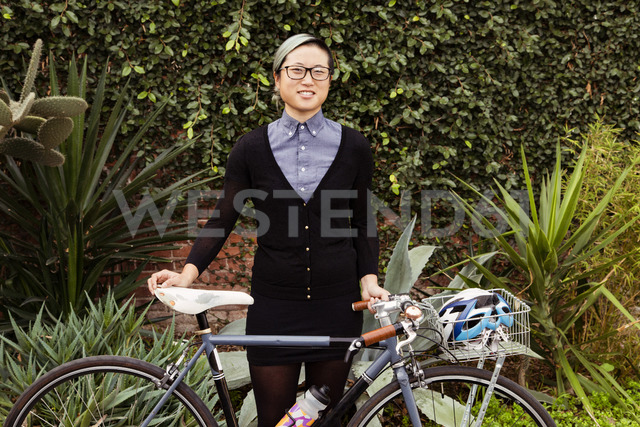 Portrait of happy businesswoman standing with bicycle against plants - CAVF37766