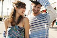 Cheerful woman looking at man holding hat on sidewalk - CAVF37769
