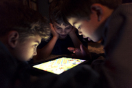 Siblings playing game on tablet computer at home - CAVF37835