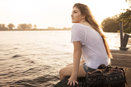 Teenage girl relaxing on pier at sunset - CAVF37949