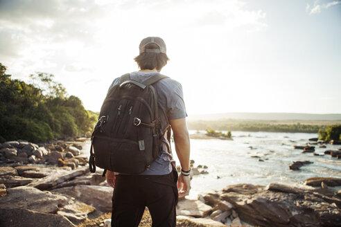 Rear view of hiker walking on rocky lakeshore - CAVF37973