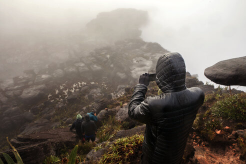 High angle view of man photographing mountain in foggy weather - CAVF37985