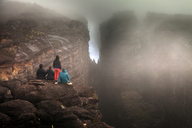 Rear view of friends sitting on rock in foggy weather - CAVF37988