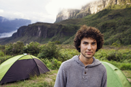 Portrait of confident man standing at campsite on mountain - CAVF38000