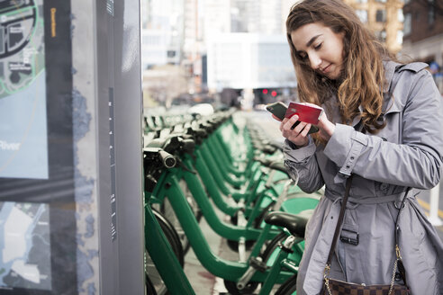 Young woman holding credit card while using smart phone by bike share at parking lot - CAVF38006