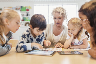 Senior teacher and children with charts and digital tablets - MASF03252