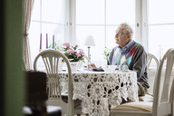 Thoughtful senior man sitting on dining table at nursing home - MASF03261