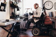 Side view of disabled musician with headphones in recording studio - MASF03267