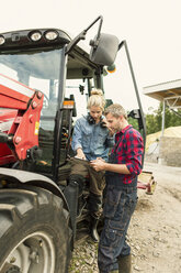 Woman discussing with male worker over document by tractor at farm - MASF03291