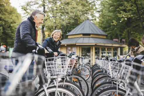 Senior people taking rental bikes at parking lot - MASF03303