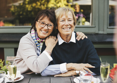 Smiling senior female friends with arm around at cafe table - MASF03309