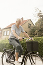 Smiling senior woman cycling on road by house - MASF03321