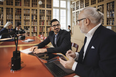 Smiling man discussing with senior lawyer at table in library - MASF03342