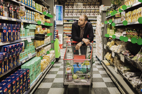 Thoughtful male customer leaning on shopping cart at supermarket - MASF03345