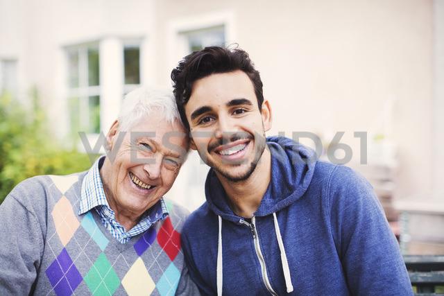 Portrait of happy senior man with caretaker sitting outdoors - MASF03348