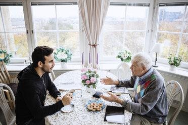 Senior man talking to caretaker at dining table in nursing home - MASF03357