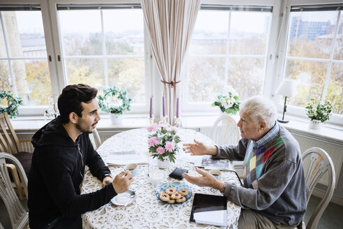 Senior man talking to caretaker at dining table in nursing home - MASF03357