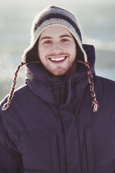 Portrait of happy young man standing outdoors during winter - MASF03360