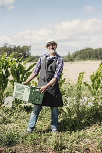 Portrait of smiling mature gardener holding crate and standing at farm - MASF03384