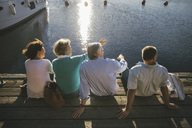 Rear view of senior couples looking at view while sitting on pier - MASF03402
