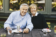 Portrait of happy senior couple having dessert at outdoor restaurant - MASF03405