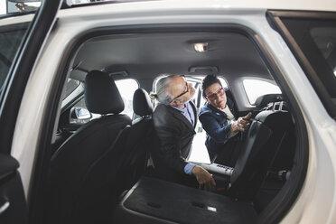 Senior man and woman analyzing new car at showroom - MASF03411