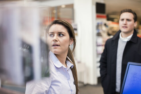 Saleswoman and male customer at cash counter in electronics store - MASF03420