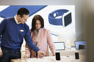 Salesman assisting customer in buying smart watch at store - MASF03423