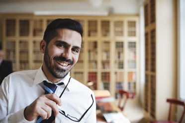 Portrait of happy male lawyer holding eyeglasses in library - MASF03435