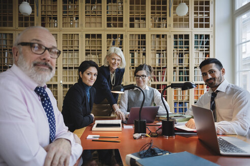 Portrait of happy lawyers at table against bookshelf - MASF03438