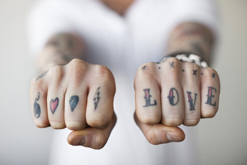 Mid section of a man showing love tattoos on his punch - MASF03459