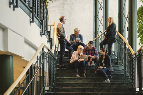 Multi-ethnic business people discussing on staircase of creative office - MASF03474