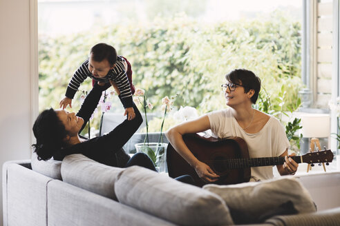 Mother enjoying with baby girl while woman playing guitar at home - MASF03477