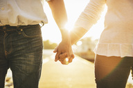 Midsection of loving senior couple holding hands on pier - MASF03489