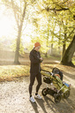 Mother with baby stroller on road against trees at park - MASF03495