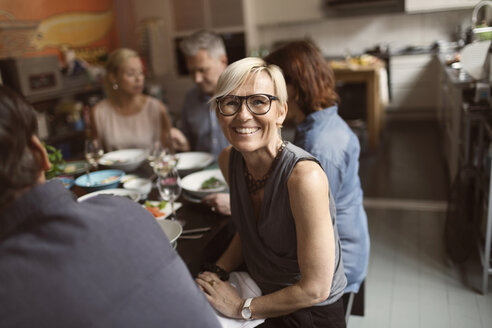 Portrait of cheerful mature woman sitting with friends at table - MASF03498
