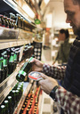 Man using bar code reader on beer bottle in supermarket - MASF03507