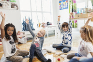 Happy children raising hands while sitting in preschool - MASF03510