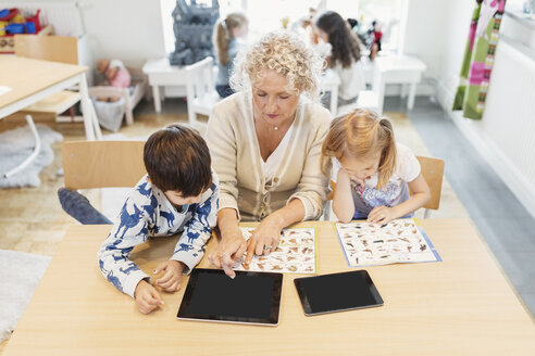 High angle view of senior teacher and children with animal charts and digital tablets - MASF03513