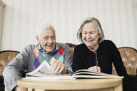 Happy senior couple reading book in living room at nursing home - MASF03522