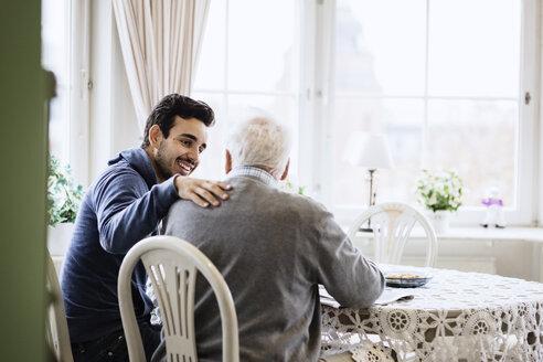 Happy caretaker communicating to senior man in nursing home - MASF03525