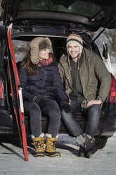 Happy couple talking while sitting on car trunk - MASF03528