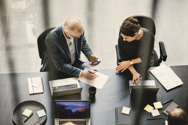 High angle view of businessman and businesswoman discussing at table in office - MASF03549