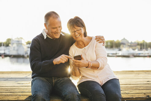 Happy senior couple using mobile phone while sitting on pier - MASF03561