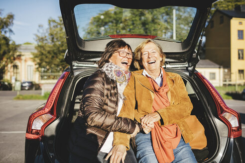 Happy senior woman sitting in opened car trunk - MASF03564