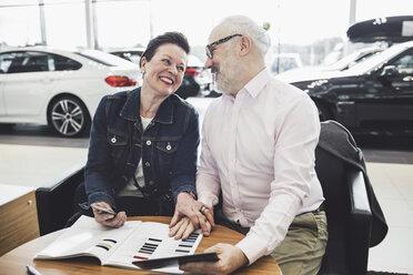 Happy senior couple reading brochure at car showroom - MASF03573