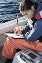 High angle view of woman examining while writing on clipboard in boat - MASF03588