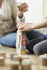 Cropped image of teacher and student stacking blocks - MASF03597